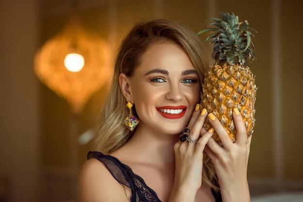 Jeune fille souriante avec soirée maquillage portant des accessoires posant et tenant des ananas, gros plan. Photo Premium