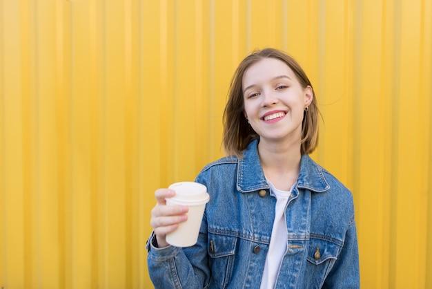 Jeune Fille Souriante Avec Une Tasse De Café Dans Ses Mains Sur Fond De Mur Jaune. Photo Premium