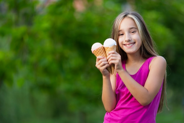 Jeune fille souriante tenant des cornets de crème glacée Photo gratuit