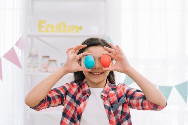 Jeune fille souriante tenant des œufs de pâques rouges et bleus sur ses yeux à la maison Photo gratuit