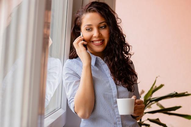Jeune fille souriante tenant une tasse de café et parler au téléphone Photo Premium