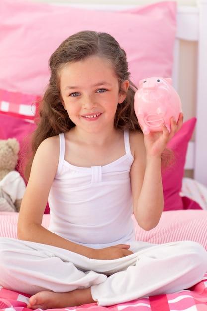 Jeune fille souriante tenant une tirelire Photo Premium