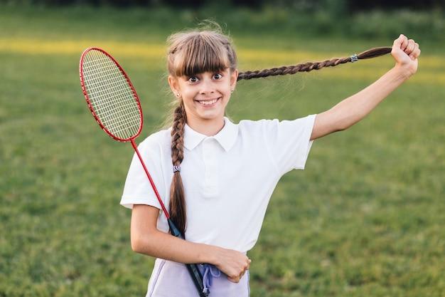 Jeune fille souriante tirant ses longs cheveux tressés tenant du badminton Photo gratuit