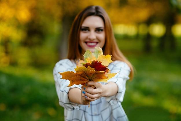 Jeune fille tenant l'automne laisse dans les deux mains dans le parc. Photo gratuit