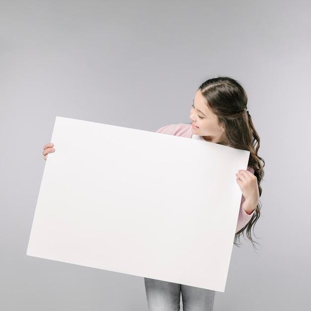 Jeune fille tenant une bannière vide Photo gratuit