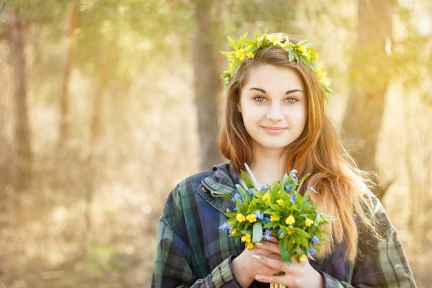 Jeune fille tenant un bouquet de fleurs de printemps Photo Premium