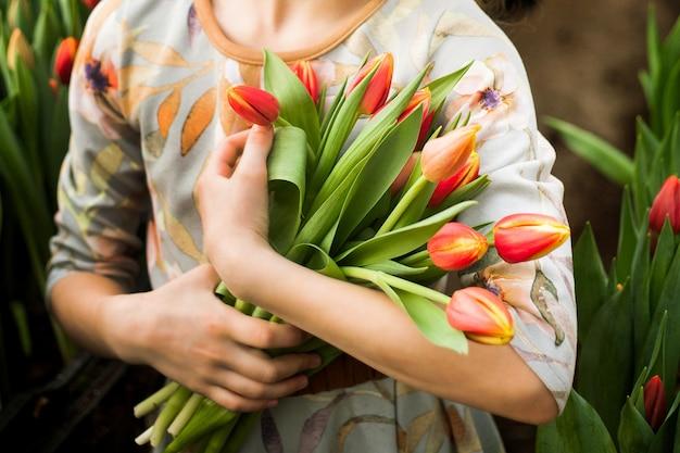 Jeune fille tenant un bouquet de tulipes cultivées dans une serre Photo Premium