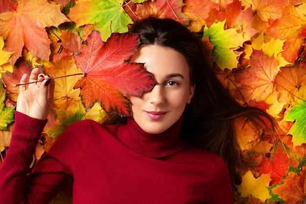 Jeune fille tenant une feuille d'érable rouge à la main sur fond coloré de feuilles mortes. Photo Premium