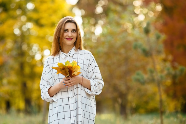 Jeune fille tenant des feuilles d'automne dans le parc. Photo gratuit