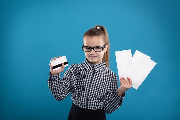 Jeune fille tenant des formulaires vierges et une carte de crédit et souriant Photo Premium