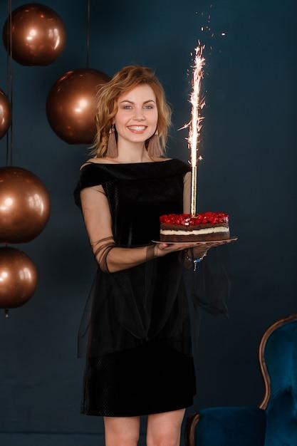 Jeune fille tenant le gâteau d'anniversaire avec feu d'artifice sur fond de mur noir. Photo gratuit