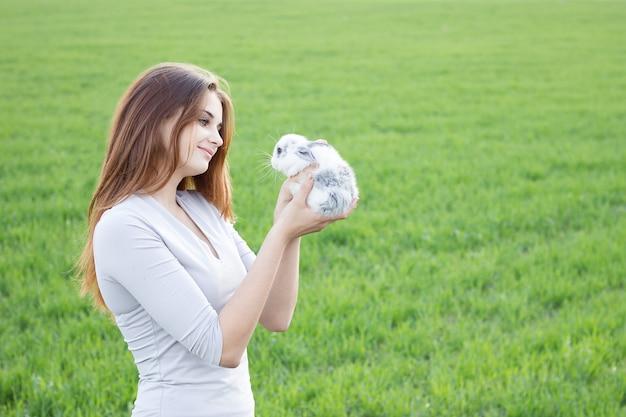 Jeune fille tenant un lapin dans un pré vert. Photo Premium