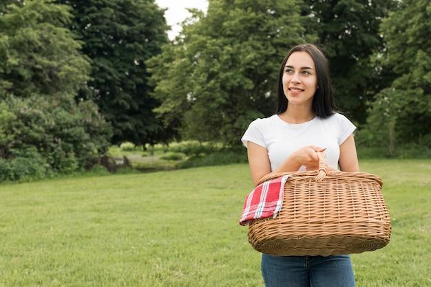 Jeune fille tenant un panier pique-nique Photo gratuit