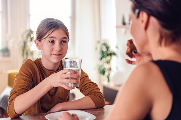 Jeune fille tenant un verre d'eau pendant le petit déjeuner Photo Premium
