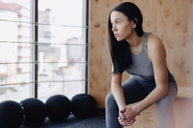 Jeune fille en tenue de sport dans une salle de sport dans un contexte simple, un thème de fitness, de crossfit et de sport Photo Premium