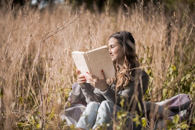 Jeune Fille Sur Un Terrain Lisant Un Livre Photo gratuit