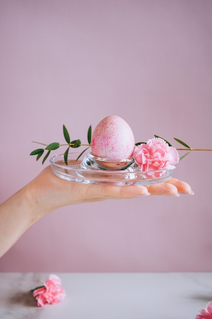 La jeune fille tient un oeuf de pâques rose sur un support, fond rose et marbre, minimalisme, fleurs Photo Premium