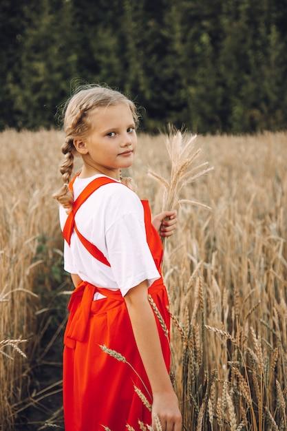 Une Jeune Fille Avec Des Tresses Et Une Robe Rouge Se Promène Dans Un Champ De Blé Photo Premium