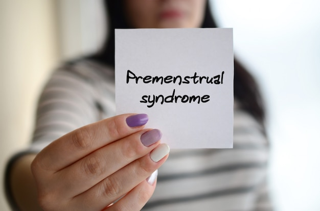 Jeune fille triste montre un autocollant blanc syndrome prémenstruel Photo Premium