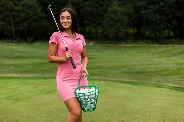 Jeune fille en tshirt rose sur le parcours de golf Photo gratuit