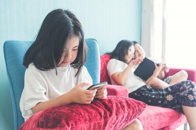 Jeune Fille Utilise Un Smartphone Sur Une Chaise Mère S'amusant Avec Son Frère Sur Un Canapé à La Maison Photo Premium