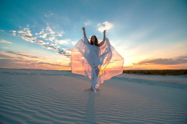 Jeune fille vêtue d'une robe blanche volante danse et pose dans le désert de sable au coucher du soleil Photo Premium
