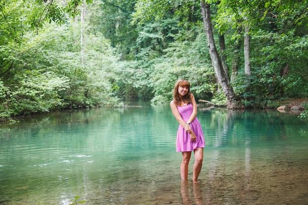 Jeune fille vêtue d'une robe courte rose marche sur une rivière dans la forêt Photo Premium