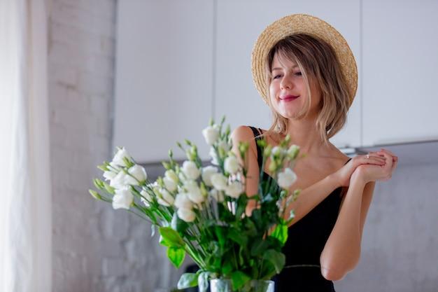 Jeune fille vêtue d'une robe noire près de bouquet de roses blanches dans un vase Photo Premium