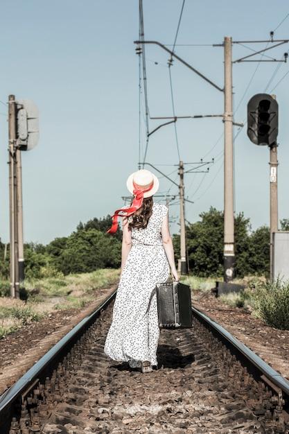 Jeune fille avec une vieille valise sur la voie ferrée. Photo Premium