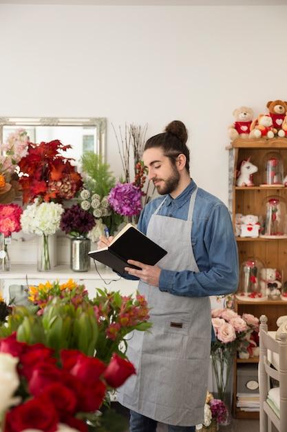 Jeune fleuriste mâle debout dans le magasin de fleurs écrivant dans le journal avec un stylo Photo gratuit