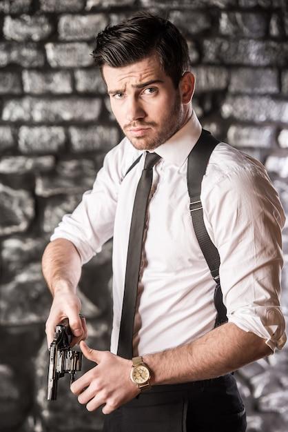 Jeune gangster confiant tire le revolver de l'étui. Photo Premium