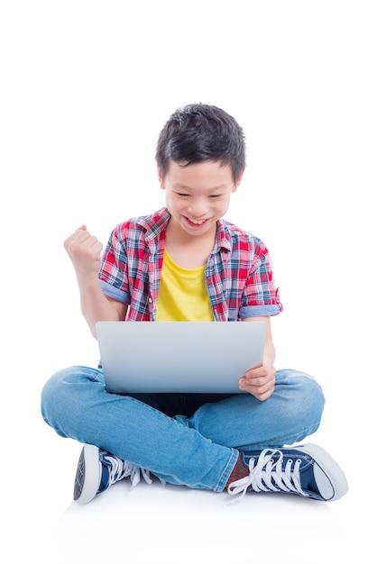 Jeune garçon asiatique assis sur le sol et jouer à des jeux sur ordinateur portable sur fond blanc Photo Premium