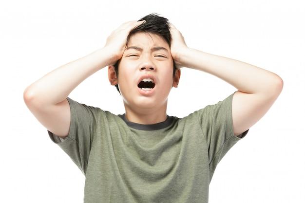 Jeune garçon asiatique sur fond blanc, soyez contrarié; avoir un mauvais caractère émotionnel. Photo Premium