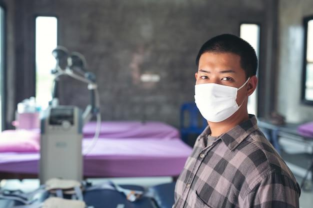 Le Jeune Garçon Avertit Le Masque, Ressent Une Douleur Thoracique Et Est Assis à L'hôpital Pour Rencontrer Un Médecin. Photo gratuit