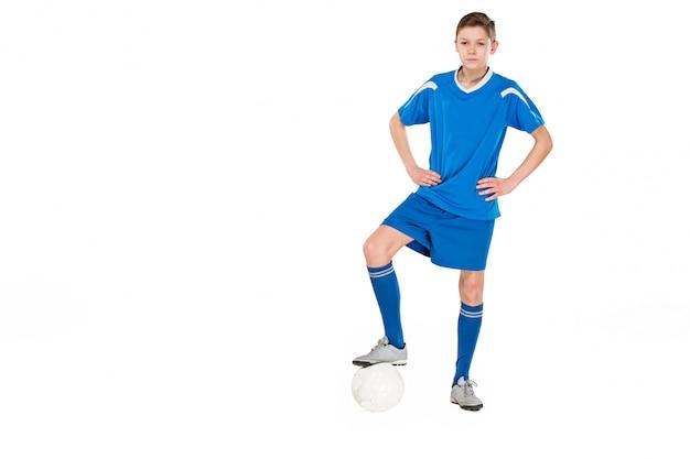 Jeune Garçon Avec Un Ballon De Soccer Faisant Voler Coup De Pied Photo gratuit