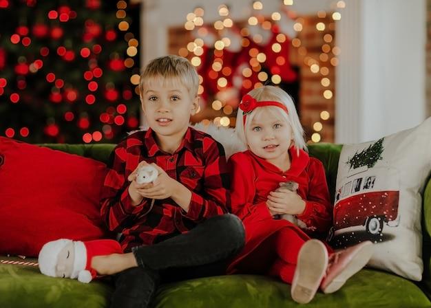 Jeune Garçon Blond Mignon En Chemise Carrée Rouge Et Jolie Fille En Robe Rouge Assis Sur Un Canapé Vert Photo Premium