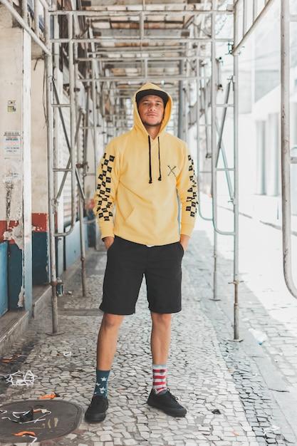 Jeune Garçon élégant Dans Les Rues Sous Un échafaudage Photo gratuit