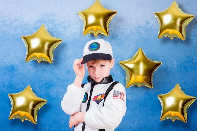 Jeune garçon garçon jouant dans un astronaute en costume d'astronaute blanc et rêvant de voler dans le cosmos à travers les étoiles en restant à proximité des ballons de l'étoile d'or Photo Premium