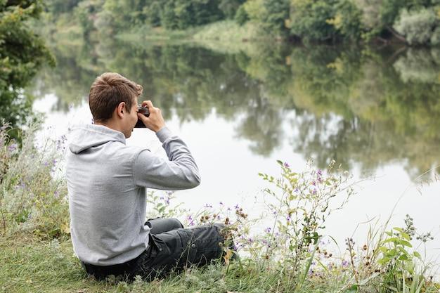 Jeune garçon prenant des photos près du lac Photo gratuit