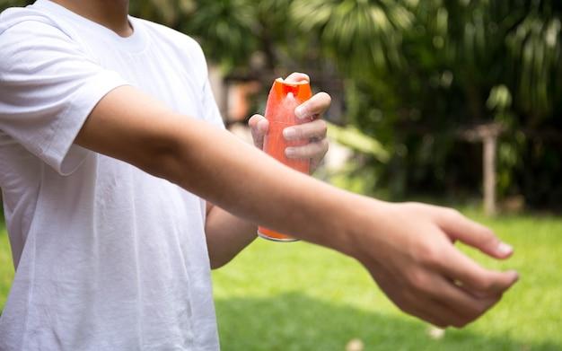 Jeune garçon, pulvérisation d'insectifuges sur la peau avec un flacon pulvérisateur Photo Premium