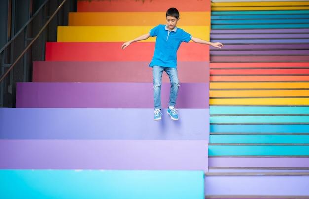 Jeune Garçon Sautant Sur L'escalier Arc-en-ciel Coloré Photo Premium