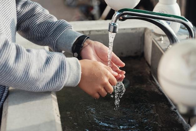 Jeune garçon se lave les mains dans l'évier Photo Premium