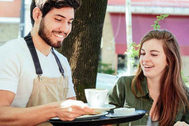 Jeune garçon servant du café à une cliente Photo Premium
