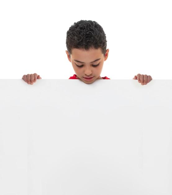 Un jeune garçon tenant un tableau blanc avec espace de copie Photo Premium