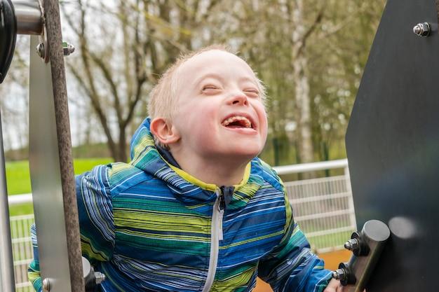 Jeune garçon trisomique jouant dans une cour de récréation Photo Premium