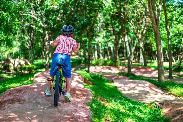 Jeune garçon à vélo dans le jardin Photo Premium