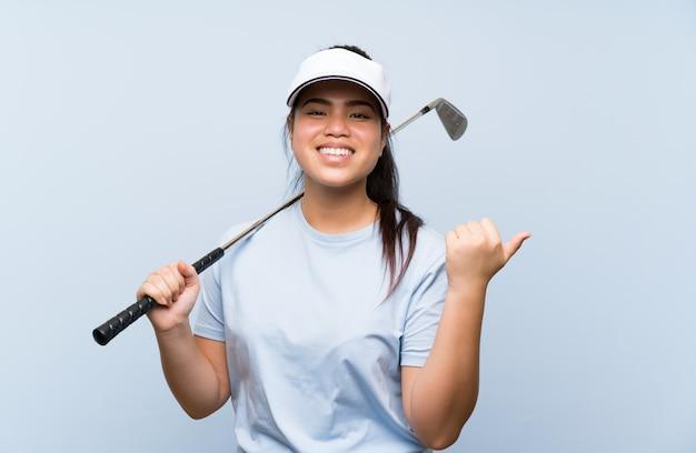 Jeune golfeuse asiatique fille sur mur bleu isolé pointant sur le côté pour présenter un produit Photo Premium