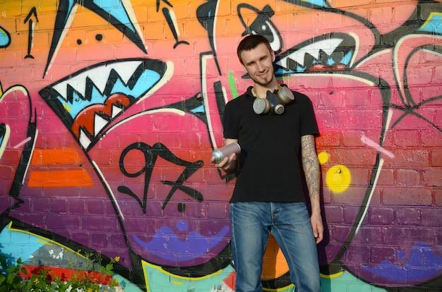 Jeune Graffeur En T-shirt Noir Avec Aérosol Argenté Peut Près De Graffitis Colorés Photo Premium