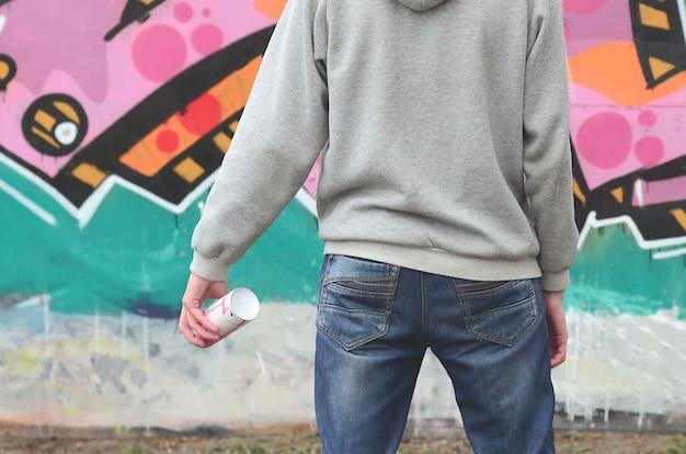 Une jeune graffeuse à capuchon gris regarde le mur Photo Premium