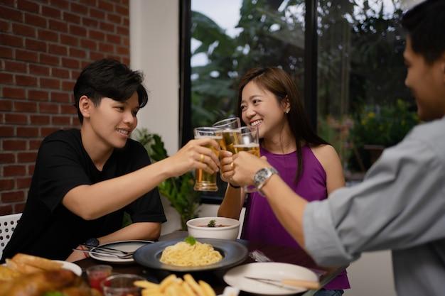 Un Jeune Groupe Asiatique Boit De La Bière Et Des Verres Clink Dans Un Restaurant. Photo Premium